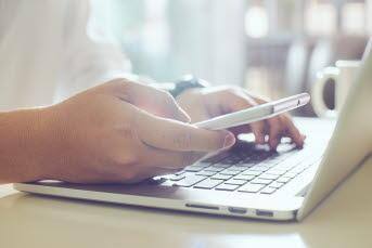Bild på en person som använder en smartphone och en bärbar dator.