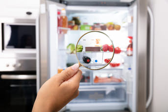 Bilden föreställer en hand som håller i ett förstoringsglas vid ett öppnat kylskåp