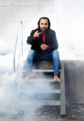 Bilden föreställer skådespelaren Özz Nûjeni som sitter i en trappa