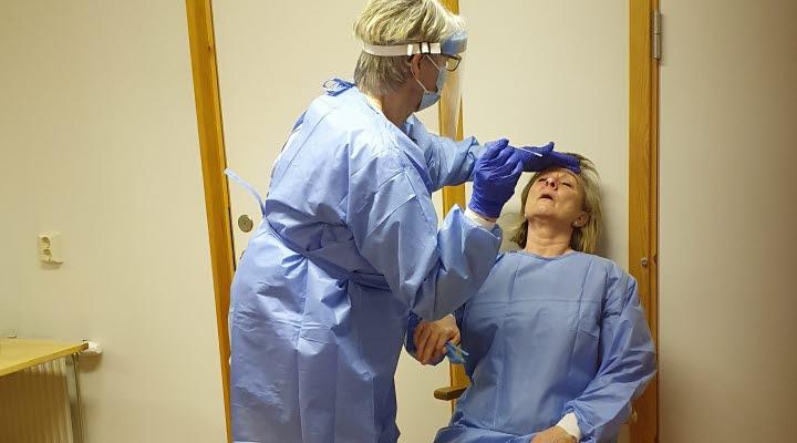 En kvinna lutar sig över en annan kvinna och provtar henne i näsan med en bomullspinne. Båda kvinnorna är klädda i blåa arbetskläder och kvinnan som provtar har mask och visir över ansiktet.