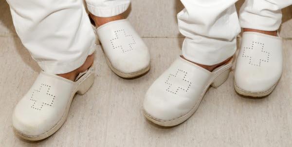Bilden visar två par fötter i vita arbetstofflor med vårdsymbol på