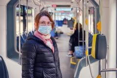 Kvinna med munskydd åker buss.